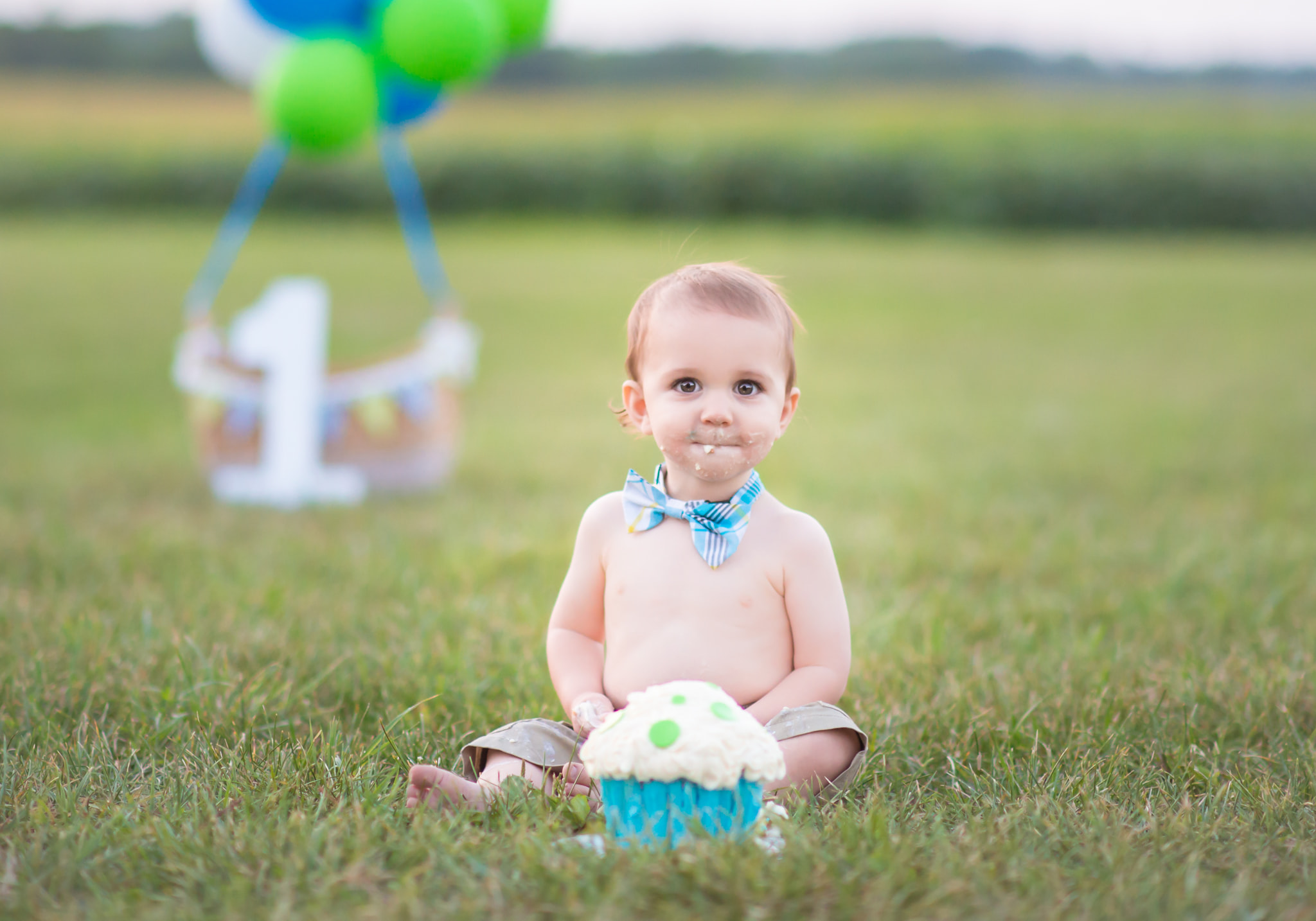 Boy eating a cake for first birthday session with hot air balloon theme