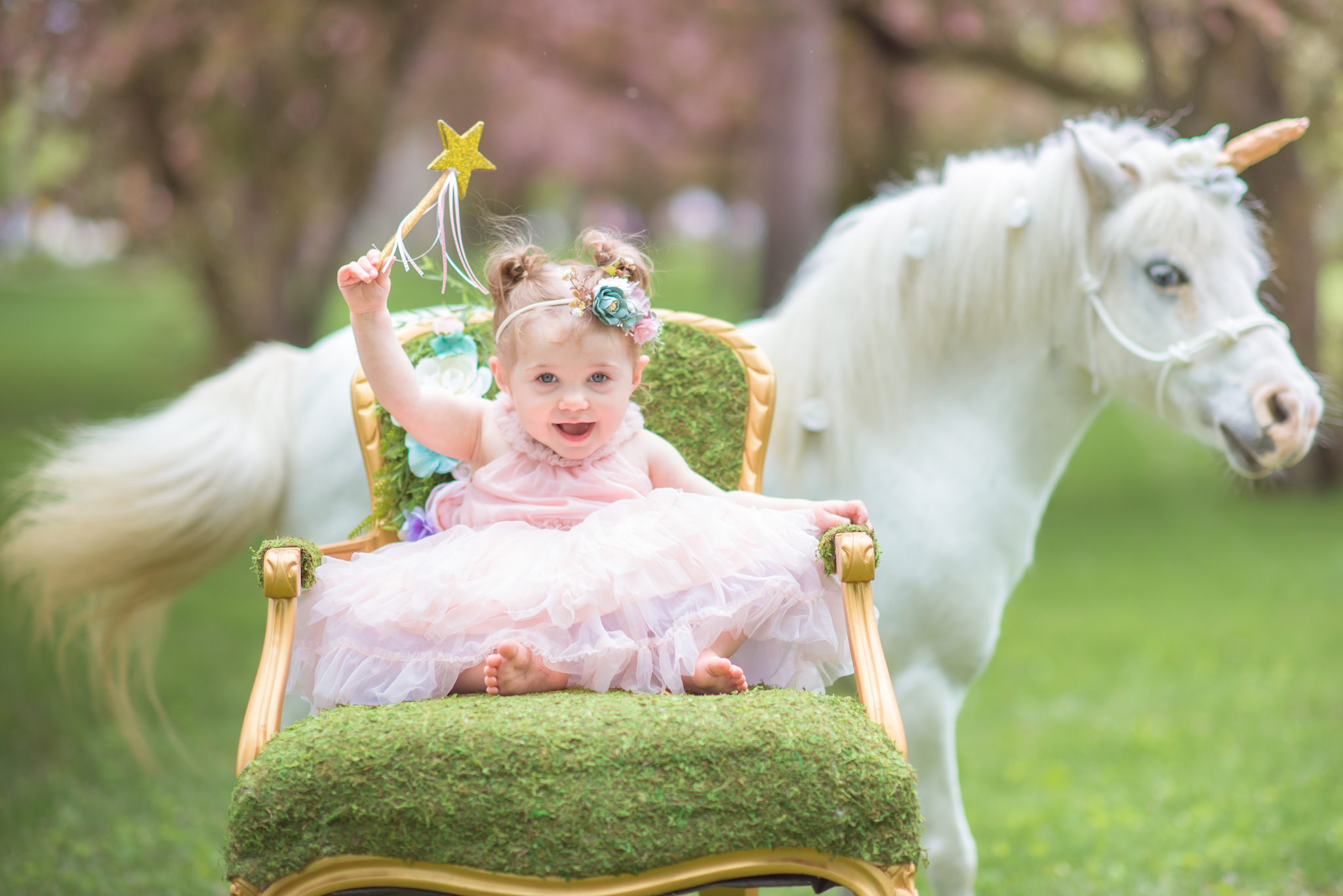 Girl holding up a gold wand next to a unicorn