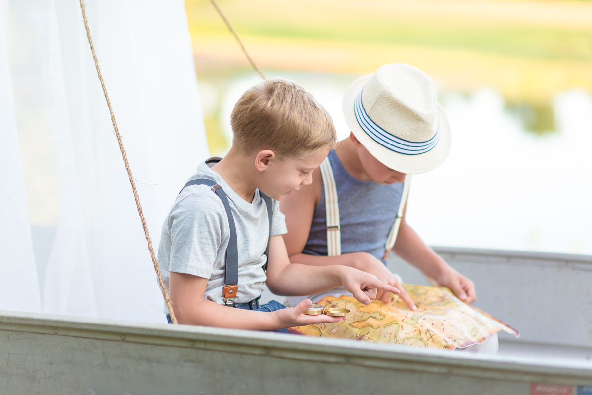 Two boys looking at map during boy adventure mini session