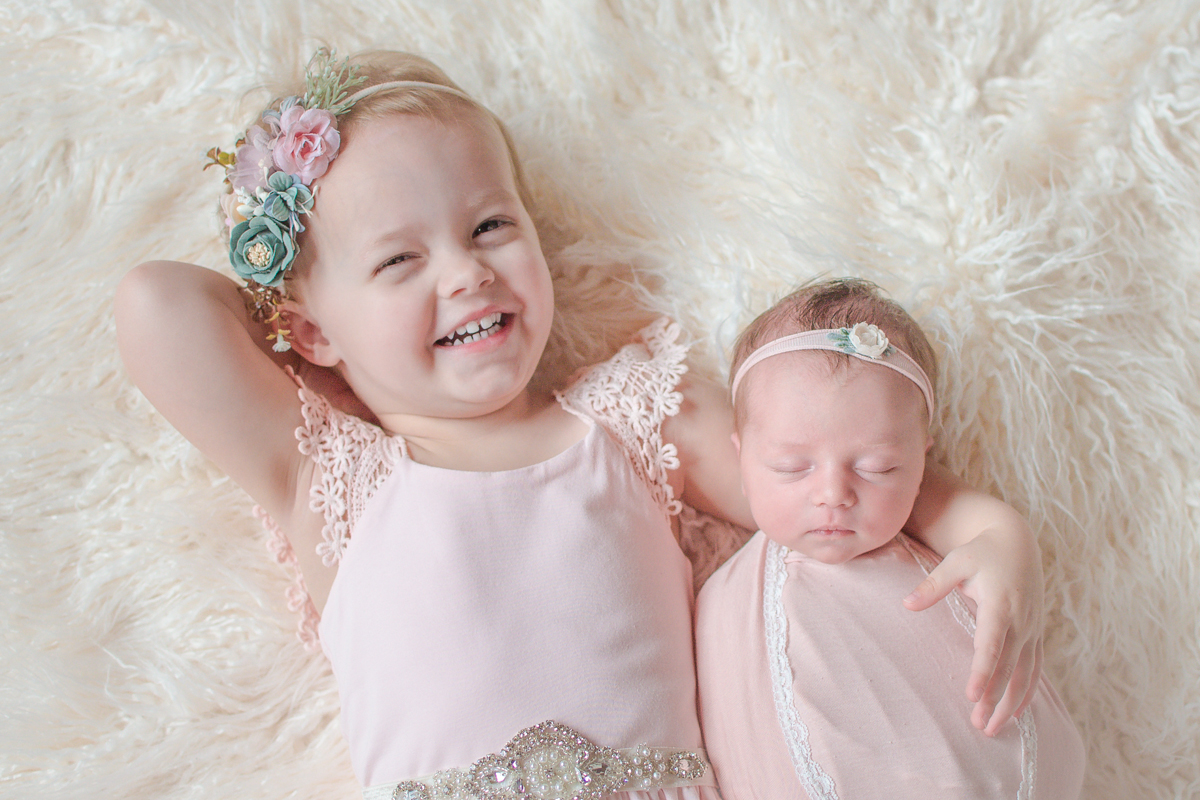 Newborn baby girl with big sister smiling in pink
