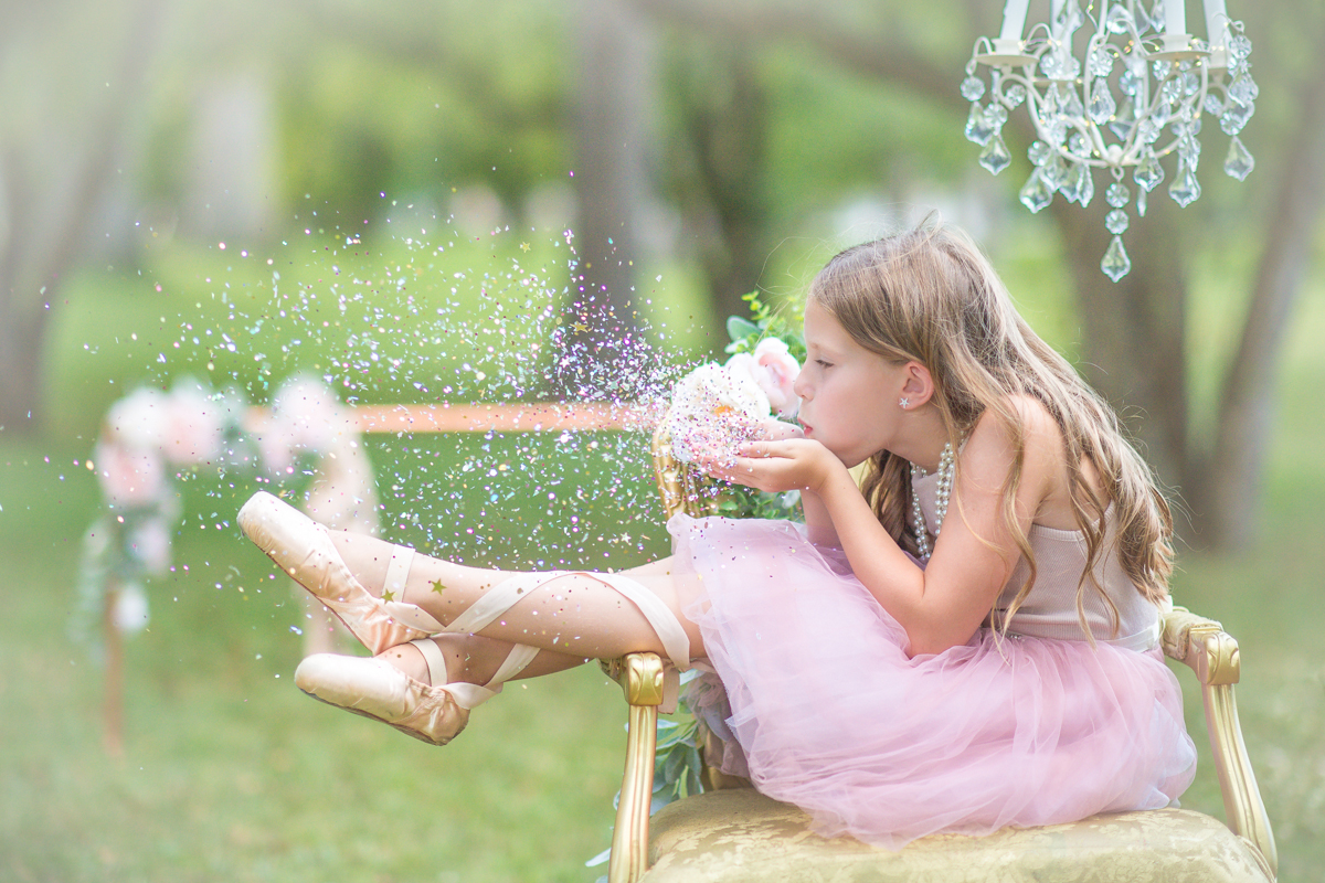 Ballerina blowing glitter during styled child session