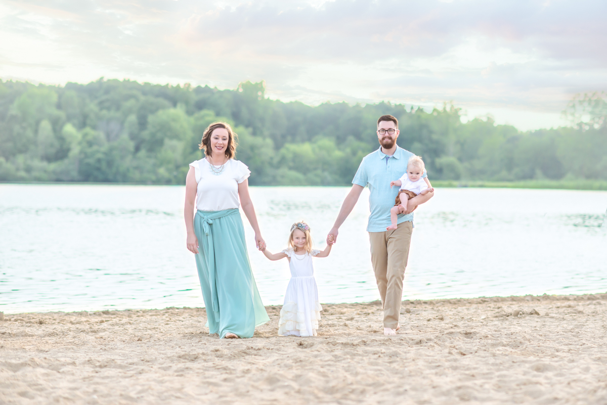 Family of 4 walking on beach in Holly MI