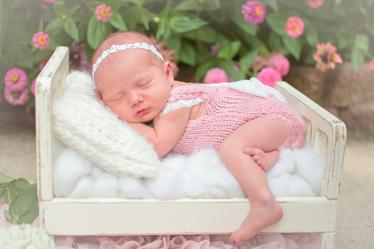 Newborn baby girl laying in bed outdoors in front of flowers