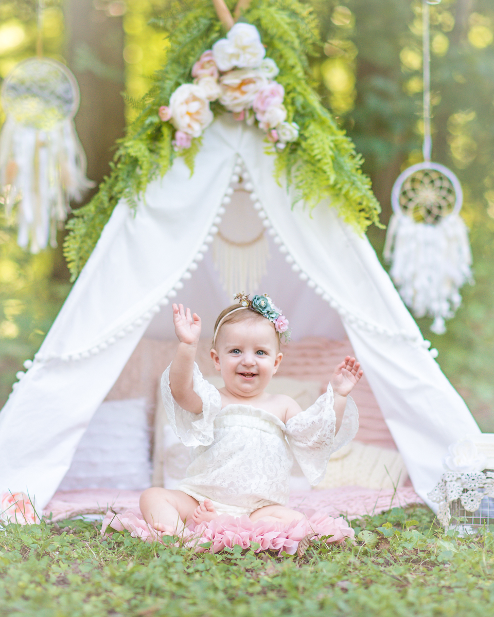 Little girl smiling in white floral teepee