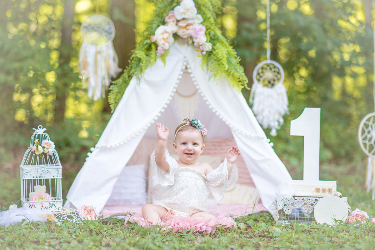 outdoor first birthday session with floral teepee