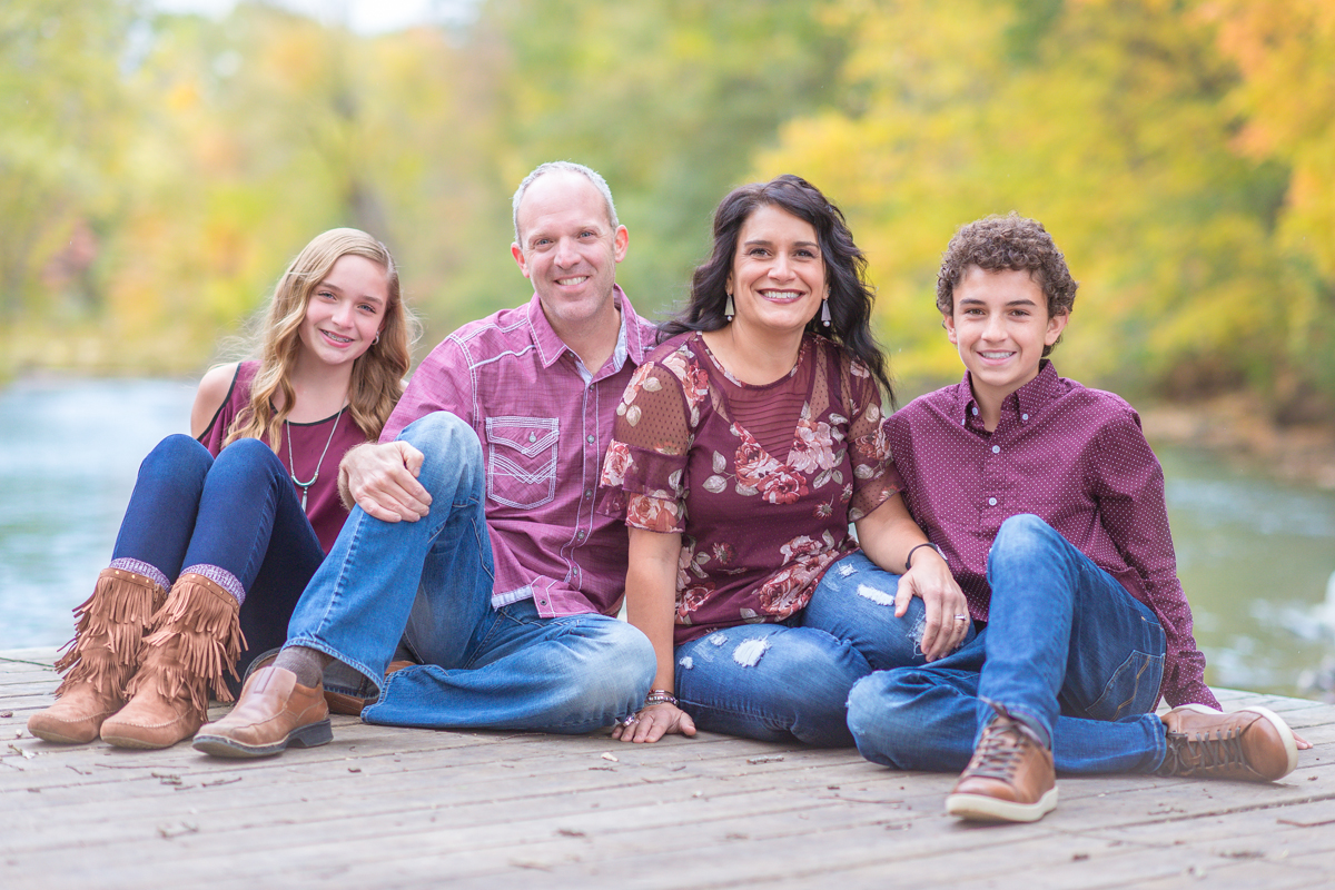 Family of four smiling while sitting on dock